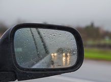 Driving in rain with side mirror in drops Stock Photo