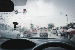 Driving in rain on street. View from car window, blurry raindrops on window and cars Royalty Free Stock Images