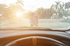 Driving in rain at sunset. Road view through car window with rain drops Royalty Free Stock Photo