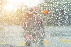 Driving in rain at sunset. Road view through car window with rain drops Royalty Free Stock Images
