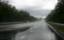 Driving in the rain V. Highway in the rain. Focus on the waterdrops on the windshield, the highways is blurred stock photos
