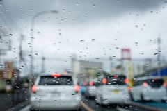 Rainy and gloomy day on the road with cars and traffic and rain is focused on the car`s windshield. royalty free stock images