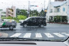 Rainy and gloomy day on the road with cars and traffic and rain is focused on the car`s windshield. stock photos