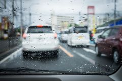 Rainy and gloomy day on the road with cars and traffic and rain is focused on the car`s windshield. stock photography