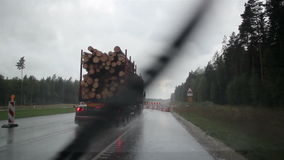 Driving on a rainy day while passing an underconstructed highway. Driving on a rainy day while passing an under-constructed highway. Truck carrying logs at the stock video