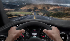 Driving in rainy weather. View from the driver angle while hands on the wheel. Rain splashed windshield Royalty Free Stock Image