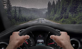 Driving in rainy weather. View from the driver angle while hands on the wheel. Rain splashed windshield.  royalty free stock photography