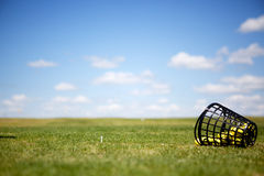 Driving Range. A tee and yellow golf balls on a driving range Stock Image
