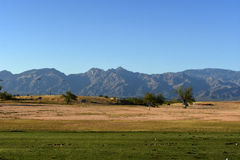 At the driving range. Driving range with mountains as background Stock Image
