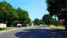 Driving residential city road with lush trees during summer day. Driver point of view pov along beautiful sunny street. Driving residential city road with lush stock video footage
