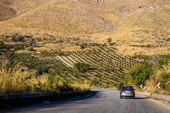 Driving on road through arid sicilian landscape Royalty Free Stock Photography