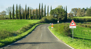 Driving road bends road sign that indicates the curve Stock Photography