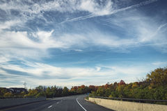 Driving on a road with trees. Driving shot, vehicle point-of-view, sunny day with wonderful sky Stock Photo
