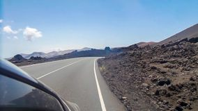 Driving on a road among volcanic landscape of Lanzarote, Canary islands, Spain stock video footage