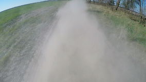 Driving on rural dusty road. The camera is outside and aimed back. stock video footage