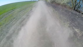 Driving on rural dusty road. The camera is outside and aimed back. stock footage