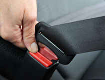 Driving Safety. Closeup of a woman's hand as she fastens a seat belt stock image