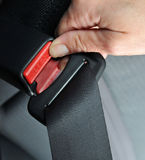 Driving Safety. Closeup of a woman's hand as she fastens a seat belt Royalty Free Stock Photos