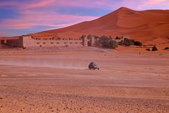 Driving through the Sahara Desert in Morocco at sunset. Driving through the Sahara Desert in Morocco Africa at sunset Royalty Free Stock Images