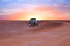 Driving through the Sahara desert in Morocco at sunset Stock Photography