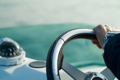 Driving sailing. A hand with a steering wheel rudder Stock Images