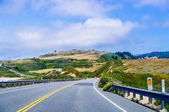 Driving on the scenic Highway 1 (Cabrillo Highway) on the Pacific Ocean coastline close to Davenport, Santa Cruz mountains visible. In the background; San stock photo