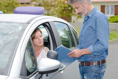 Driving school teacher stood outside car talking to female learner. Learner royalty free stock image