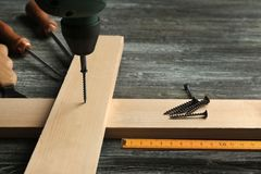 Driving nail into wooden board royalty free stock photo