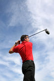 Driving Shot. Young golfer hitting an iron against a half cloudy sky Stock Images