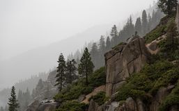 Rainy day in the mountains with rocky cliff and silhoueted trees. royalty free stock photos