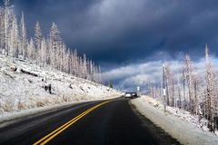 Driving through Sierra Mountains, close to Lake Tahoe on a winter day; menacing storm clouds background; California stock photography