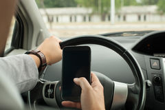 Driving with smart phone Royalty Free Stock Image