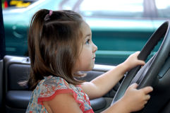 Driving and smiling. Four year old girl driving a car Stock Images