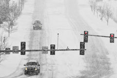 Driving on Snow and Snowy Roads in Winter Blizzard. Driving on snow and snowy roads in winter traffic lights blizzard Royalty Free Stock Photography