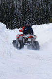 Driving a snowmobile. A view of a person riding a snowmobile with caterpillar treads through deep snow after a winter snowstorm Royalty Free Stock Photos