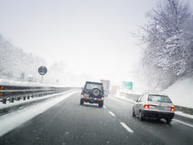 Driving through the snowy road. Vehicles on the road during a snow storm Stock Photos