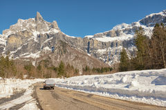 Driving on a snowy road. A pick up truck driving on a snowy road leading to a mountain Royalty Free Stock Photography