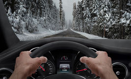 Driving in snowy weather. View from the driver angle while hands on the wheel Royalty Free Stock Photography