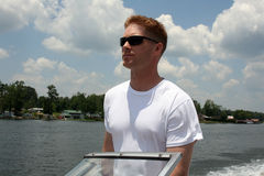 Driving the speedboat. Young man driving a speedboat accross the lake Stock Images