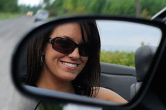 Driving A Sports Car. Pretty Woman Driving Her Convertible Sports Car With Her Sunglasses Royalty Free Stock Photos