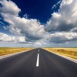 Driving on straight asphalt road at idyllic sunny day Stock Photos
