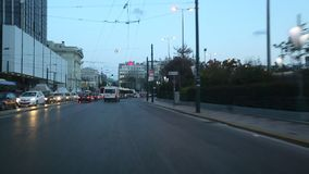 Driving on the streets at Athens in the evening time, view through the front windshield. stock video