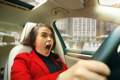 Driving around city. Young attractive woman driving a car royalty free stock photos