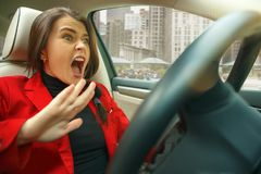 Driving around city. Young attractive woman driving a car royalty free stock images
