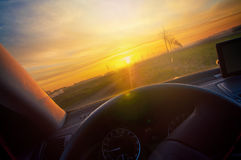 Driving at sunrise on a country road - point of view Royalty Free Stock Photography