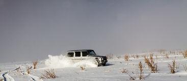 Driving SUV during snowstorm in mountains Royalty Free Stock Photos