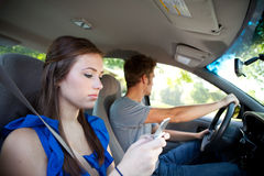 Driving: Teen Female Texts While Riding in Car Royalty Free Stock Photography