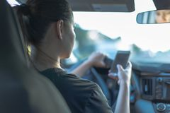 Driving and texting in car with blue tone royalty free stock photos