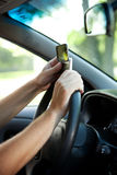 Driving: Texting While Driving. Series with two teens driving in a car.  Includes lots of images with texting and looking at cel phones while in motion Royalty Free Stock Photos
