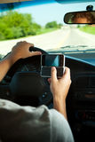 Driving: Texting While Driving. Series with two teens driving in a car.  Includes lots of images with texting and looking at cel phones while in motion Royalty Free Stock Image